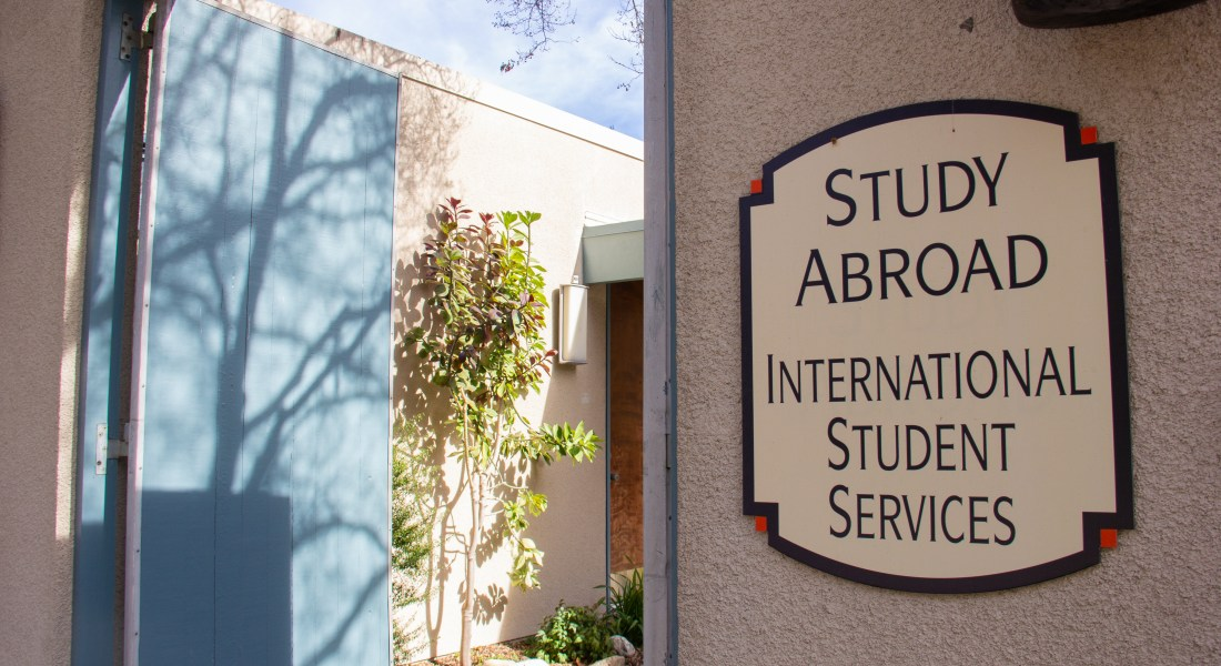 "A sign displaying ""Study Abroad: International Student Services"" is mounted on the entrance to a building with a blue door and a courtyard with trees."