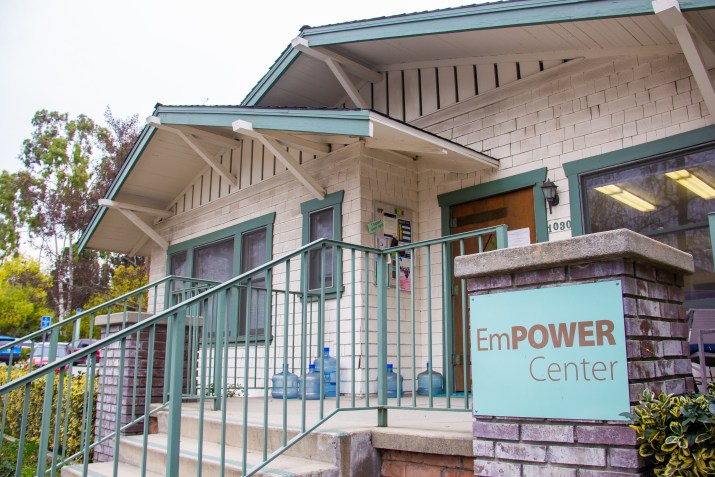 "A white and green building fills the image and features a sign that says ""EmPOWER Center."""