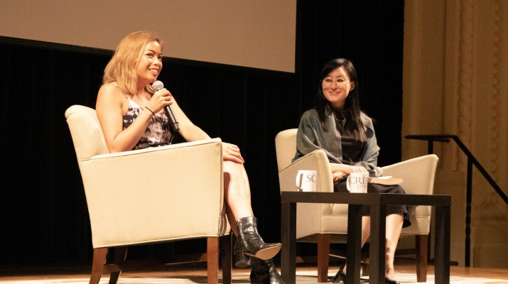 Two Asian women sit on stage with microphones; the one on the left is speaking.