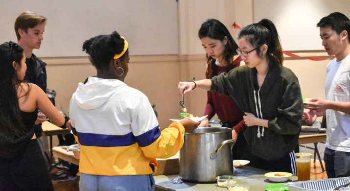 One student serves food to another student.