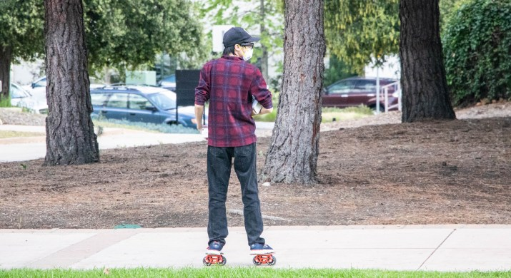 A student wearing a face mask skates through campus.
