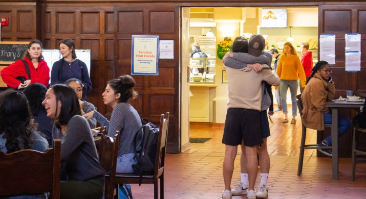 Two male students embrace to the right of the image, surrounded by other students in a dining hall.