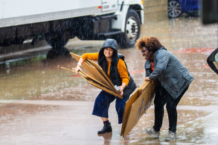 Two women have trouble holding folded-up cardboard boxes in a parking lot as rain falls around them.