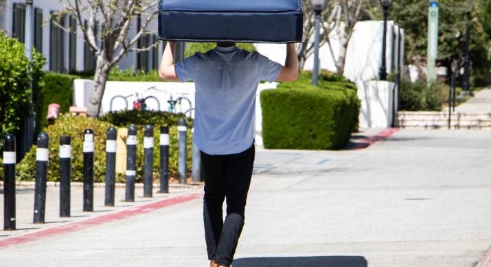 A student carrying a mattress on his head walks up a street.