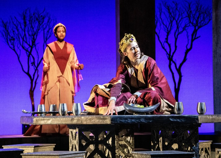 Two women wearing cloaks and crowns are on stage with one sitting on a table and the other standing behind her.