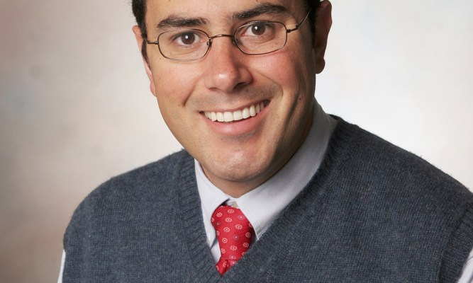 A man wearing glasses, a tie, and a sweater-vest smiles at the camera.