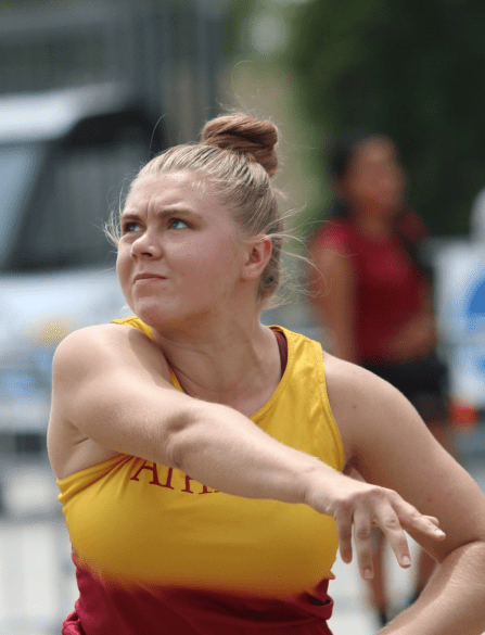 A woman looks off to the left of the image after throwing a shot put.