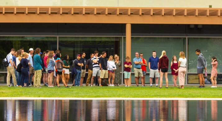 admitted students line up outside CMC's kravis center with their reflections in the pool at bottom