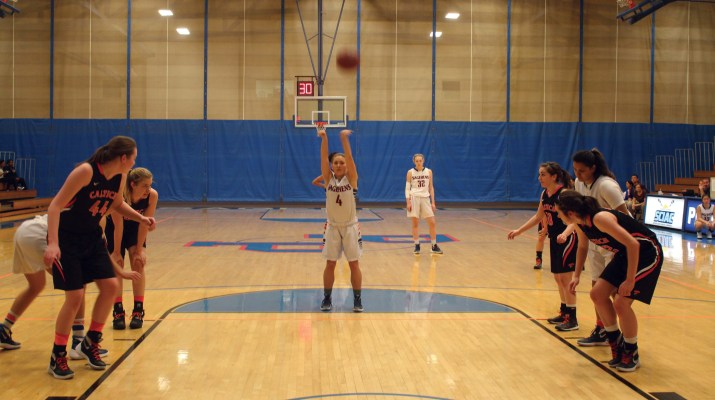 A female basketball player shoots a free throw, her hands in the air. Opposing team players line her on either side.