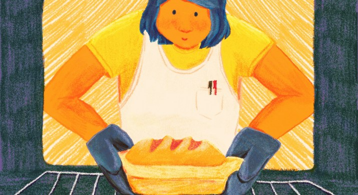 A smiling girl wearing a white apron and blue oven mitts pulls a loaf of bread out of an oven.