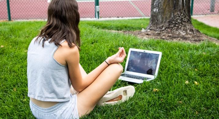 A photo of a woman meditating on grass, facing an open laptop.