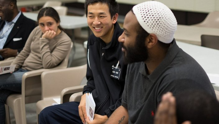 A male inmate and male college student sit together in class discussion