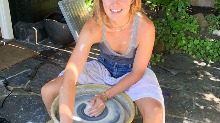 A woman sits at a pottery wheel spinning a piece of clay.