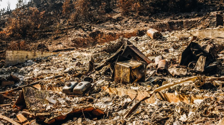 A lot that a fire has burned through. The house that existed before has been reduced to ashes and rubble. The remains of a sink and oven are visible.