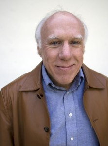 A man wearing a brown coat smiles at the camera.