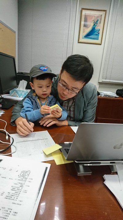 A man, with a child in his lap, grades papers.