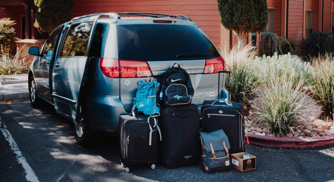 There is a blue mini van in a parking lot. It is surrounded by three black suitcases and three backpacks.