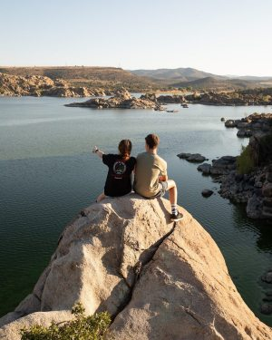 Two college students sit together on a rock overlooking a lake.