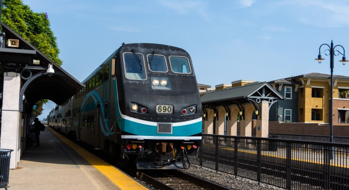 A black and teal train pulls into a station.