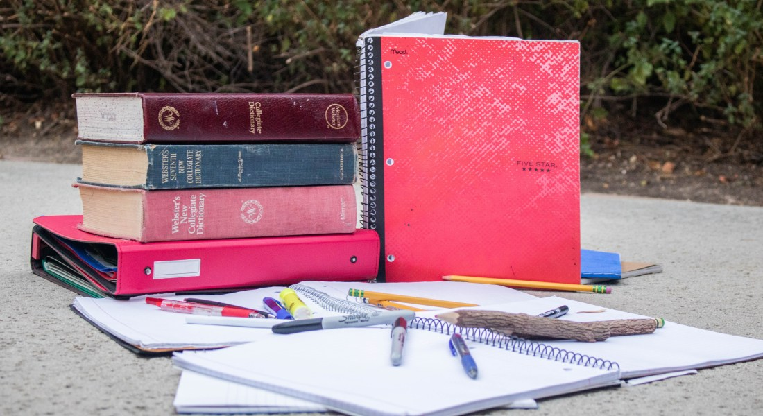 Multiple dictionaries, notebooks, and pens are stacked outside.
