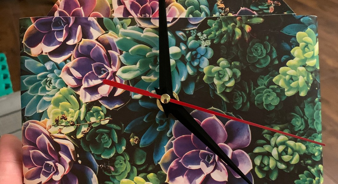 A DIY clock features photos of purple and green succulents.