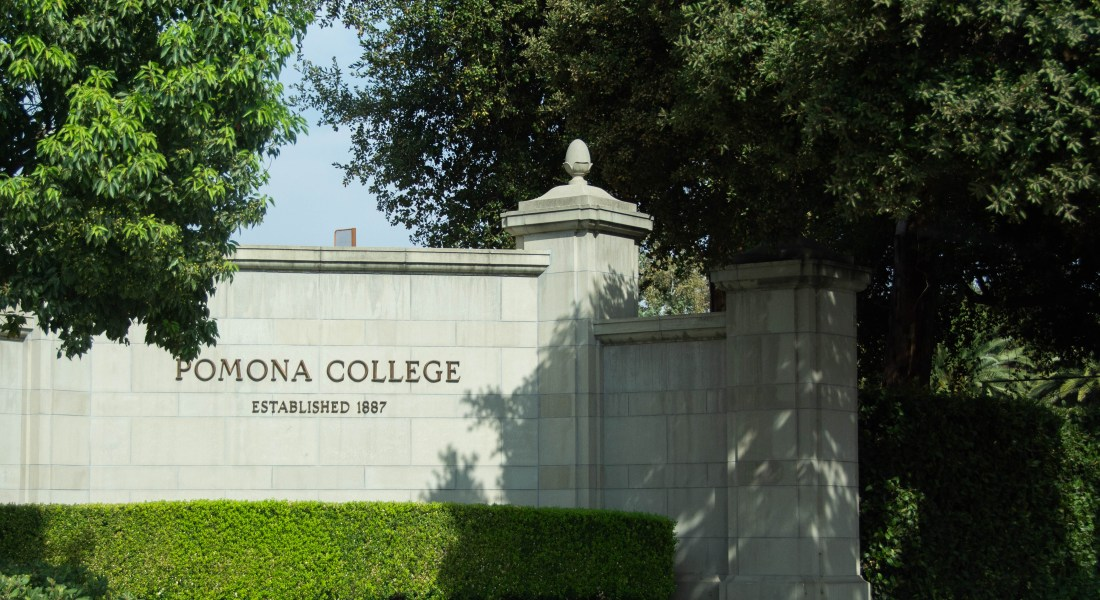 "A wall with the sign ""Pomona College Established 1887"" is surrounded by green trees."