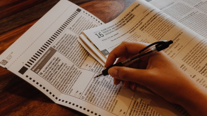 Up close photo of someone filling out a ballot that displays Proposition 16.