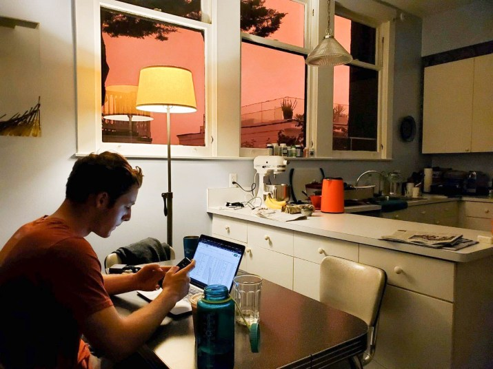 A man types on his laptop at a kitchen table.