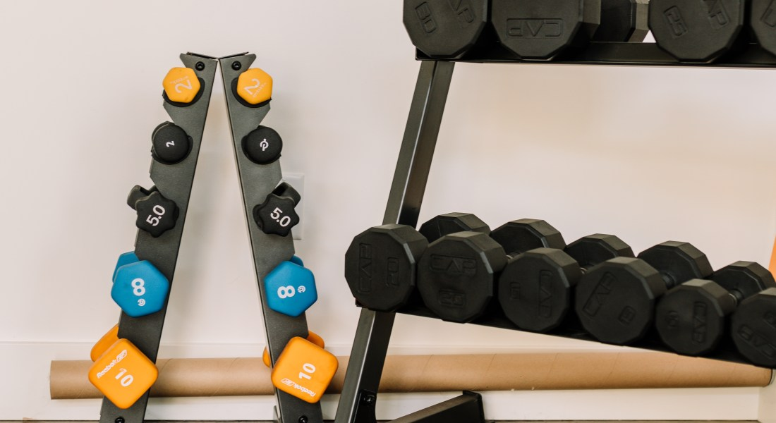 Two racks of weights sit next to each other in a home gym