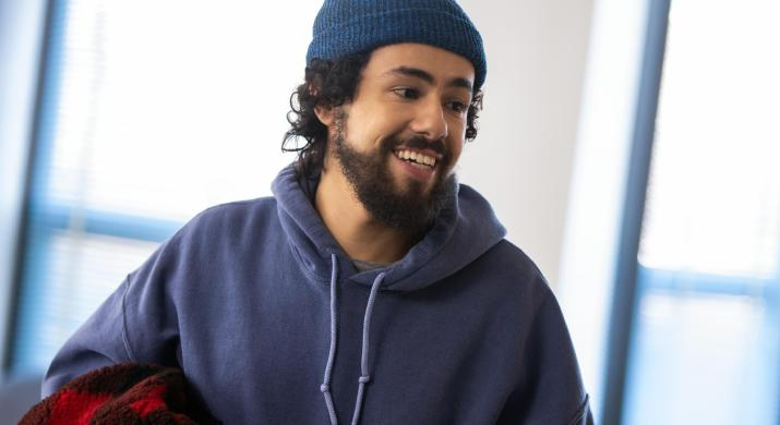 A man wearing a blue sweatshirt and a blue hat smiles off camera.
