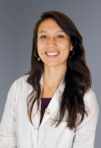 A young woman with long brown hair and a white doctor's coat smiles at the camera.