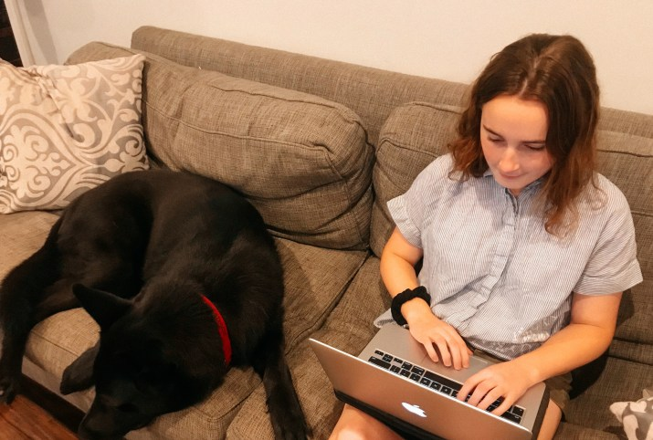 A female college student sits on a couch alongside a black dog and works on a laptop.
