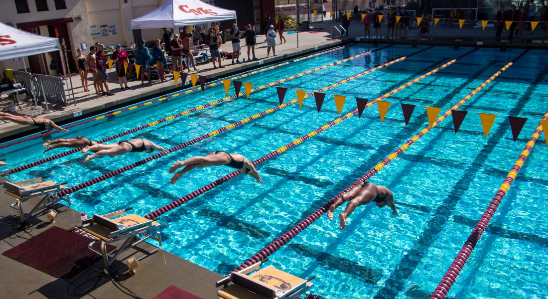 Five CMS swimmers dive into swim lanes at a swim meet.