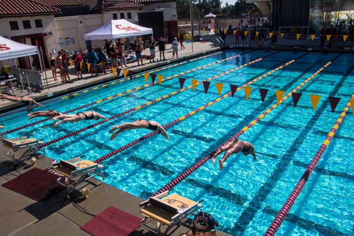 Five CMS swimmers dive into swim lanes at a swim meet.