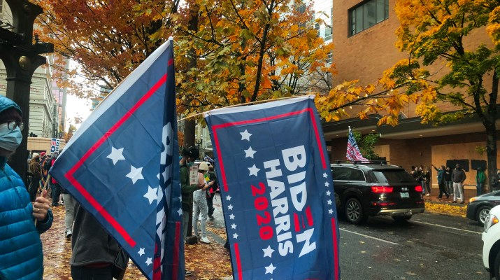 "Two people wave ""BIDEN-HARRIS 2020"" flags in Portland, Oregon."
