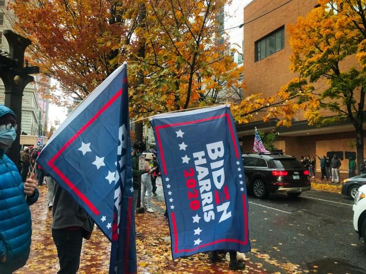 """Two people wave """"BIDEN-HARRIS 2020"""" flags in Portland, Oregon."""