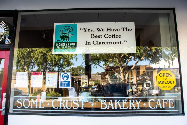 """A sign reading """"Yes, we have the best coffee in Claremont"""" sits in the window of the """"Some Crust Bakery Cafe""""."""