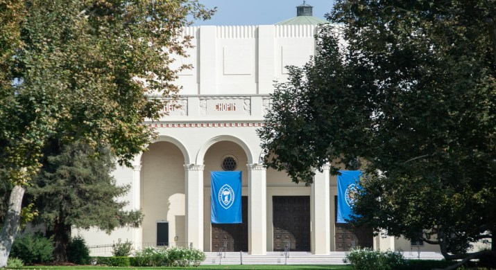 """A white building behind green trees has blue """"Pomona College"""" flags."""