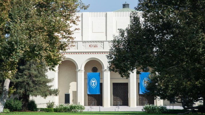 "A white building behind green trees has blue ""Pomona College"" flags."