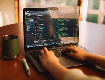 A woman is sitting at a computer writing code.