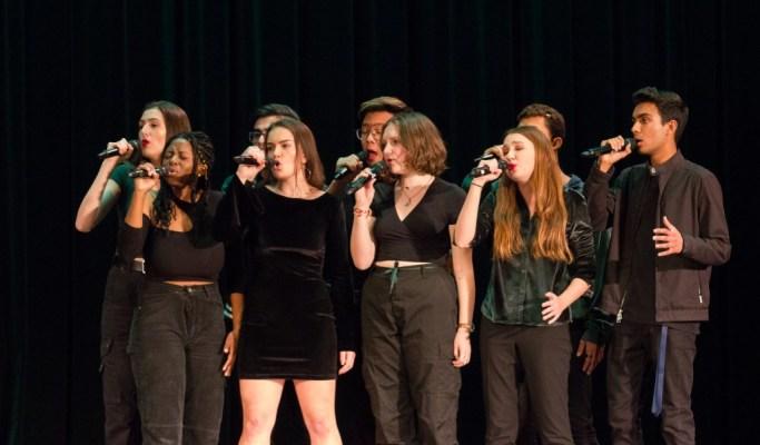 Nine people wearing black sing into microphones.