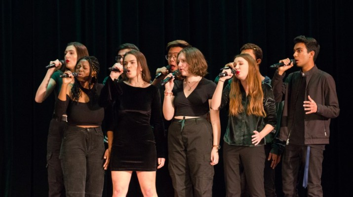 Nine people wearing black sing into microphones.