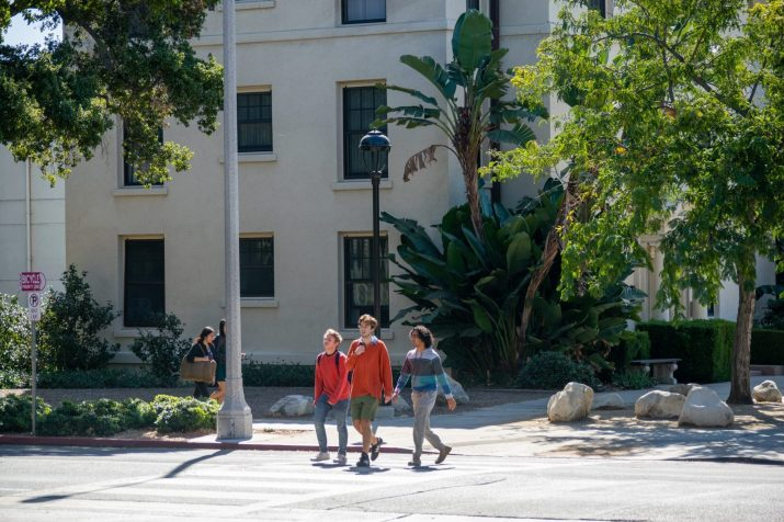 Three students cross a street