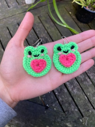 A pair of crocheted frog earrings are held in the palm of a hand