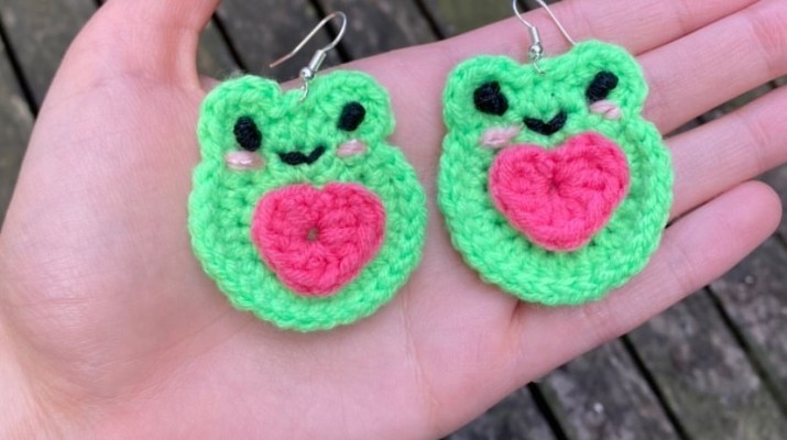 A hand holds green and pink frog earrings.