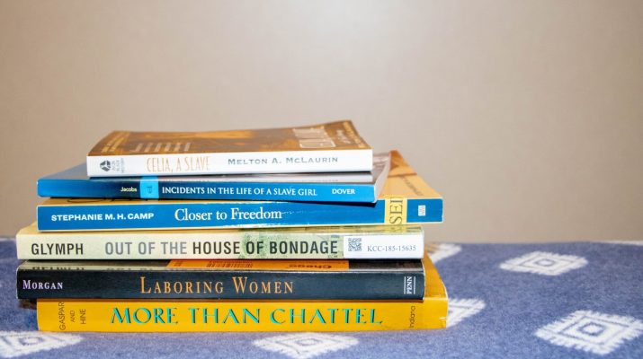 Six books with titles about slavery in the US sit on a blue blanket.