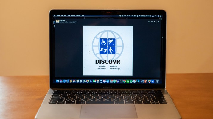 A computer on a wooden table displaying the logo of DISCOVR.
