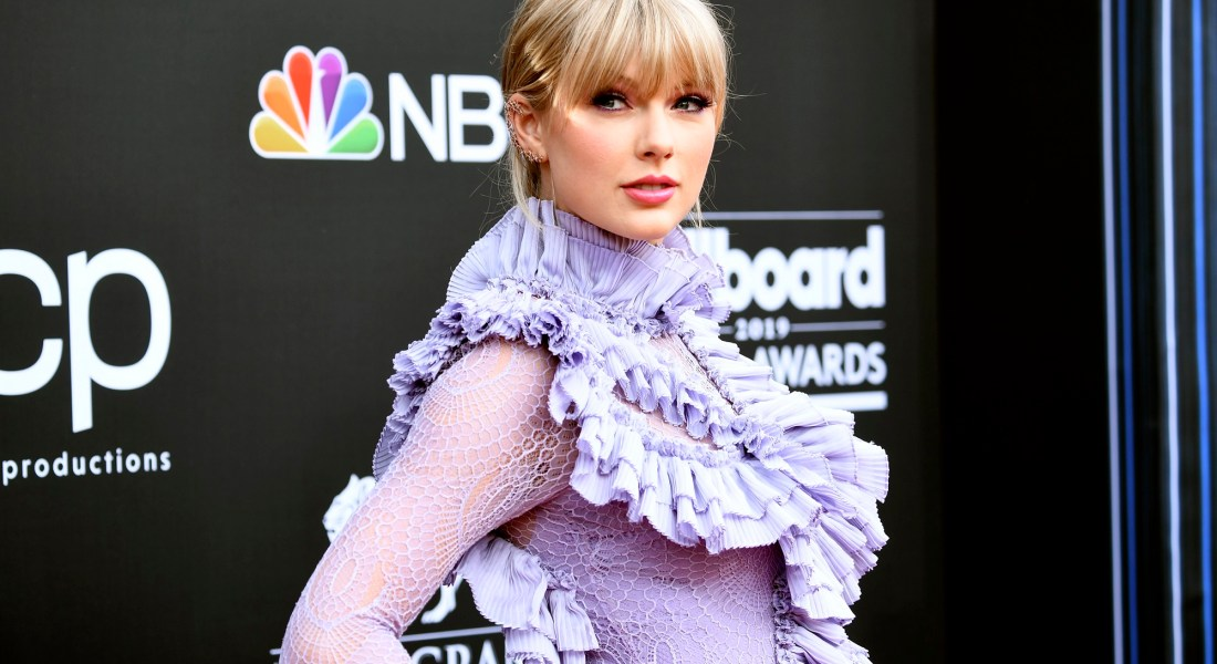 Taylor Swift at the Billboard Music Awards wearing a frilly purple dress.