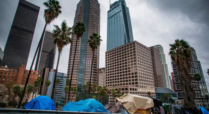 A homeless encampment is set up in front of some LA skyscapers.