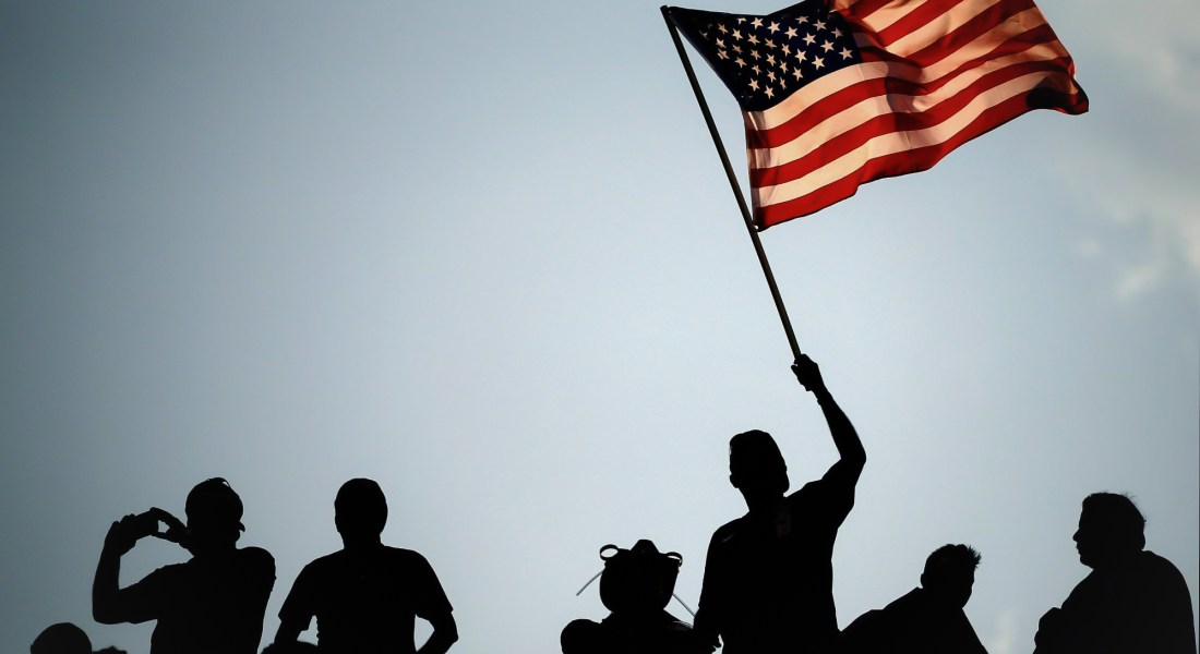 A group of people silhouetted against the sky. One of them waves an American flag.